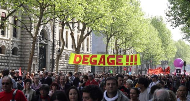 Een groepje illegalen loopt met spandoek en megafoon door Parijs. De mini-demonstratie kondigt een lente van protesten aan.