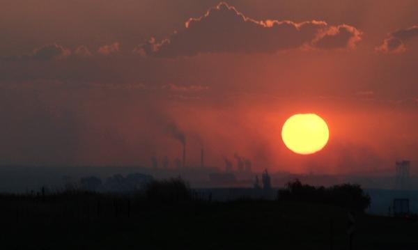 Mijnen en elekticiteitscentrales op het platteland van Zuid-Afrika bij zonsondergang.